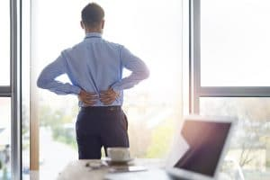Man with Scoliosis looks out window while holding his back